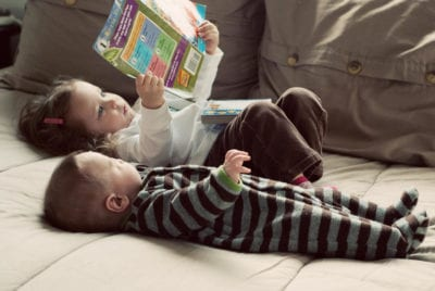 Two toddlers laying on a couch or bed reading a book.